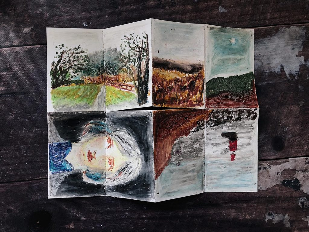 A small zine on a wooden table depicting oil pastel drawings