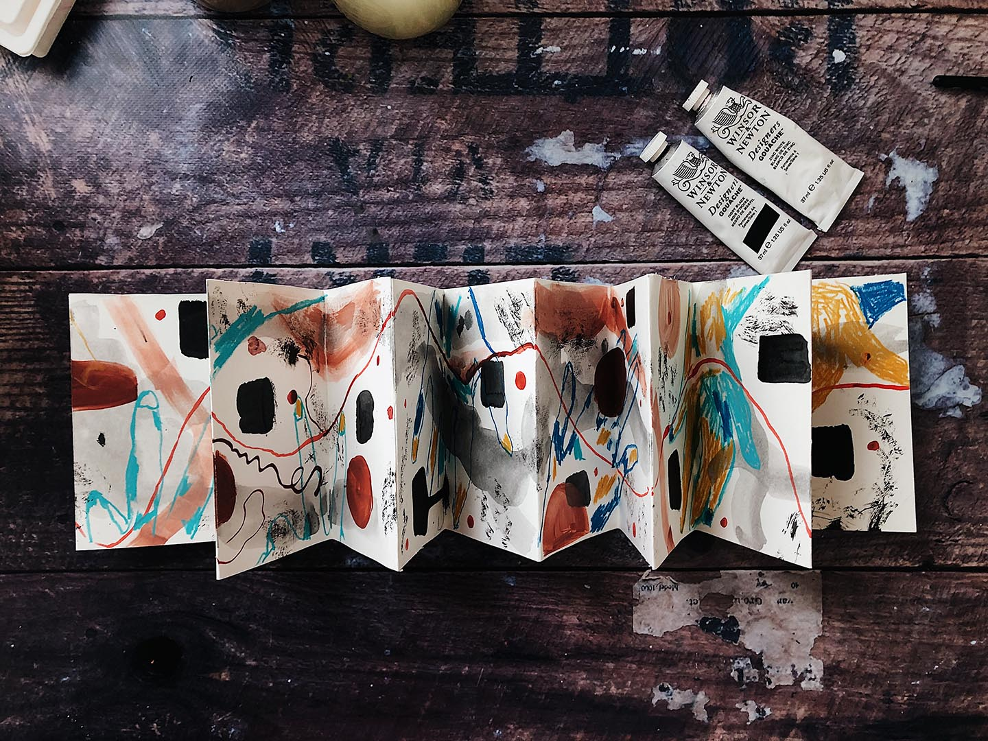 Accordion book on wooden table depicting abstract art