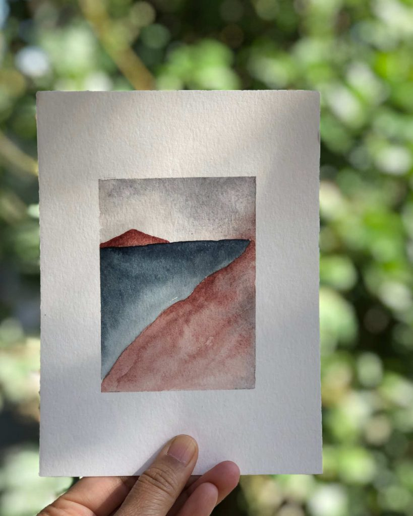 Landscape painting held against some greenery